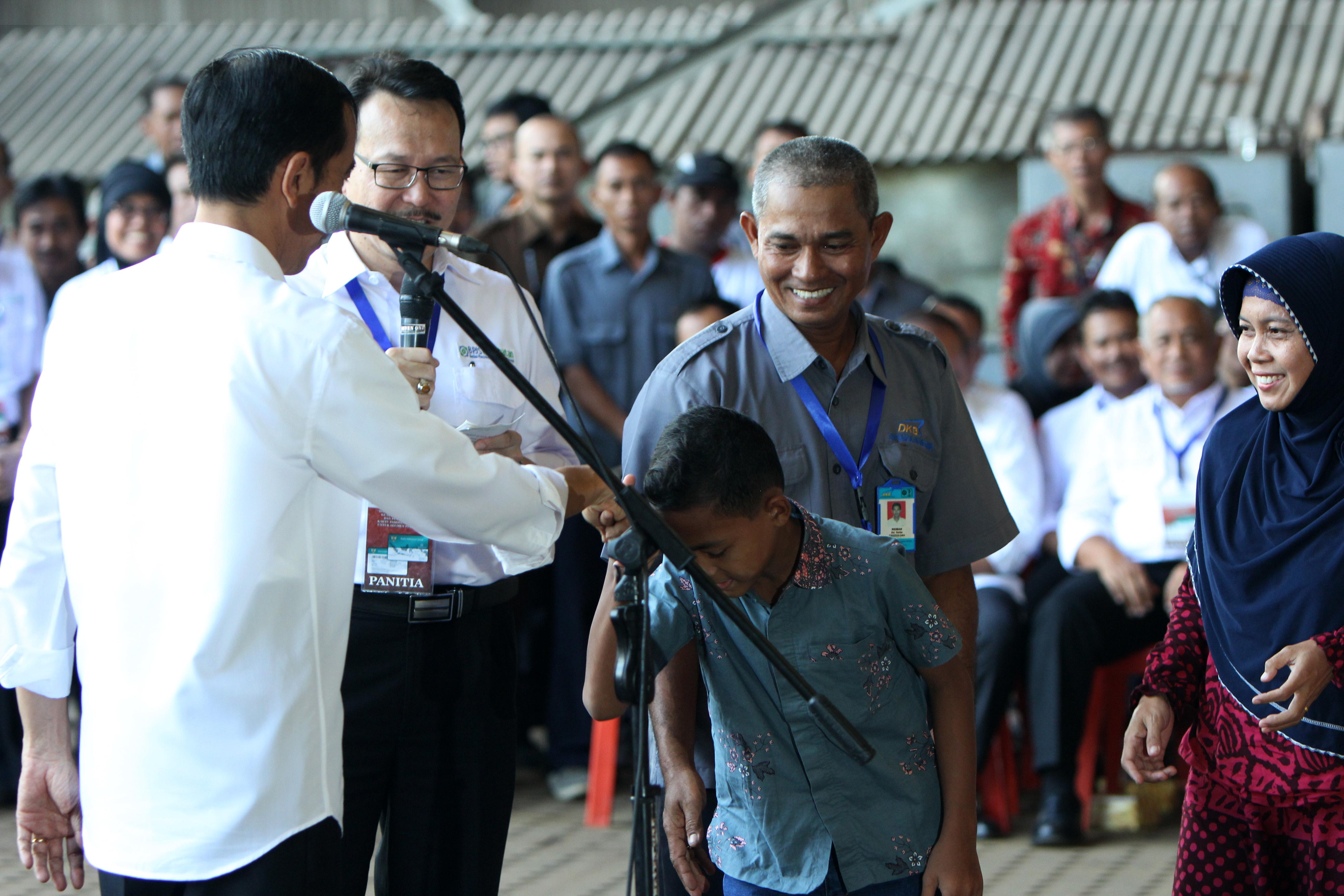Presiden Jokowi saat membagikan Kartu Indonesia Sehat kepada Pekerja PT Dok dan Perkapalan Kodja Bahari Persero bersama keluargga penerima 28 April 2015