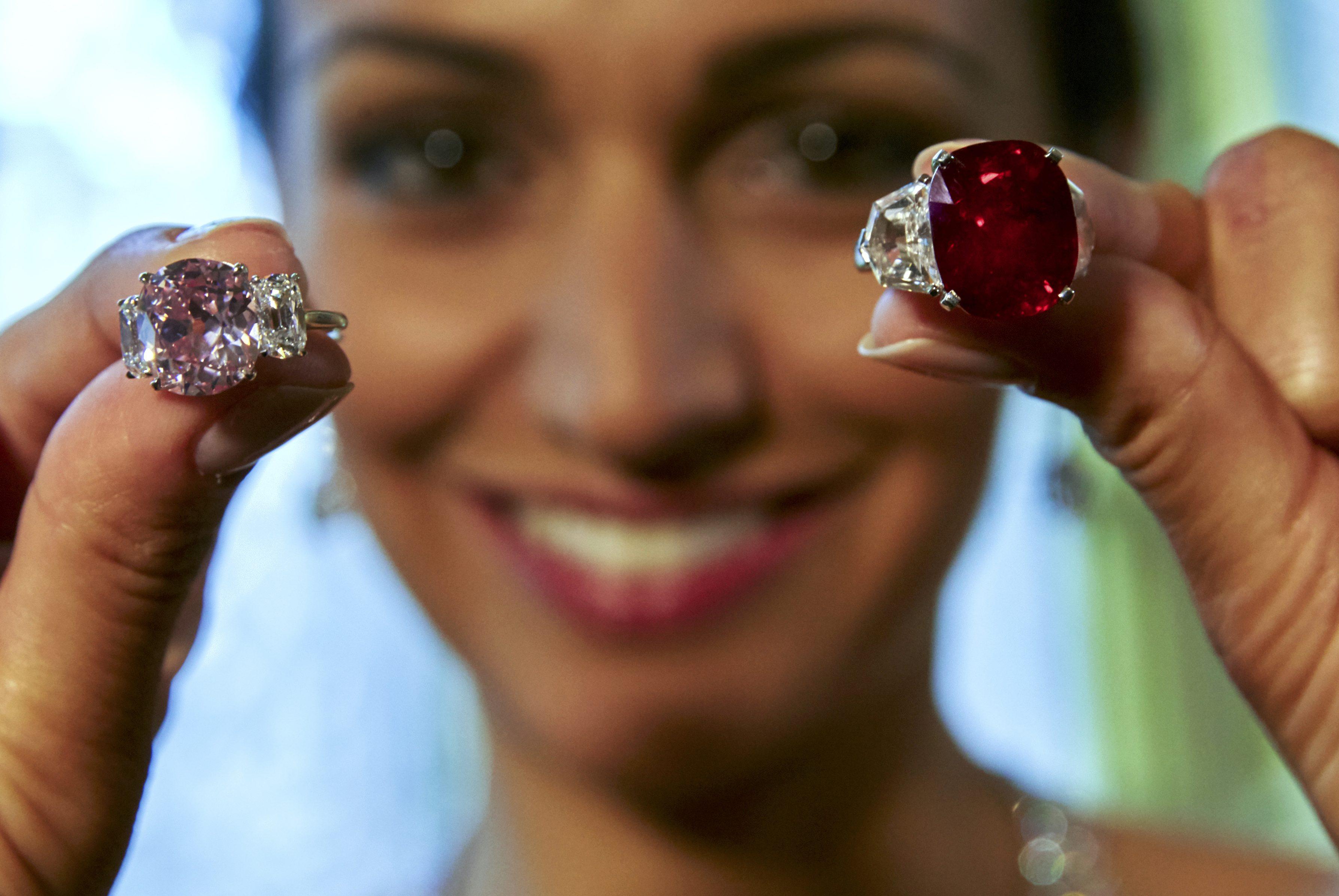 "Seorang model memperlihatkan ""Delima Matahari Terbit"" (kanan), sebuah batu delima Birma seberat 25,59 karat, dan ""Berlian Merah Muda Bersejarah"", sebuah berlian berwarna seberat 8,72 karat saat pratinjau lelang di Balai Lelang Sotheby's, Jenewa, Swiss, Rabu (6/5). Batu delima itu diperkirakan dapat terjual dengan harga sekitar 12-18 juta dolar AS (157-236 miliar rupiah), sementara berlian merah muda tersebut akan terjual sekitar 14-18 juta dolar (183-236 miliar rupiah) saat mereka dilelang di Jenewa 12 Mei mendatang. ANTARA FOTO/REUTERS/Denis Balibouse."