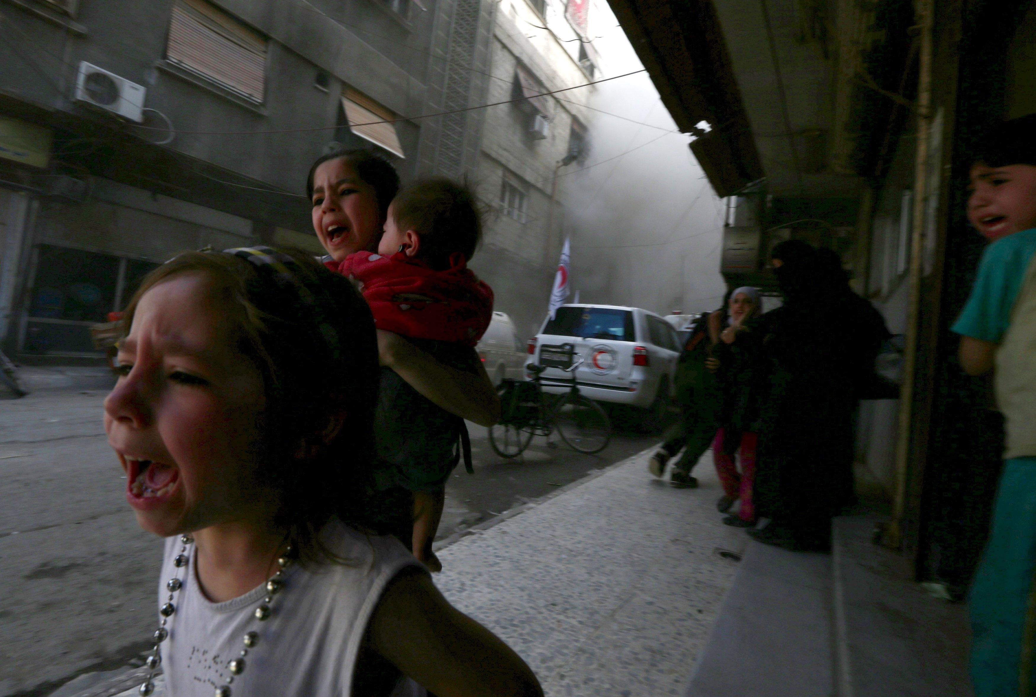 Anak-anak berteriak setelah serangan oleh pasukan yang loyal terhadap Presiden Suriah Bashar al-Assad di dekat pusat Bulan Sabit Merah Arab Suriah di Douma, Damascus, Suriah, Rabu (6/5). Serangan tersebut terjadi ketika konvoi Bulan Sabit Merah Arab mengirimkan bantuan medis ke kantor mereka di Douma, kata para aktivis. ANTARA FOTO/REUTERS/Bassam Khabieh.